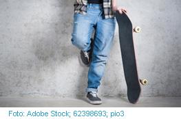 Junge lehnt an Wand mit Skateboard