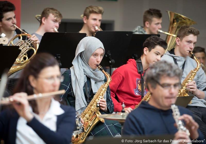 Jugendliche und Erwachsene musizieren