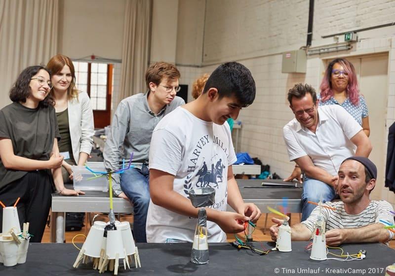 Kunstschaffende und Schüler am gemeinsamen Projekt