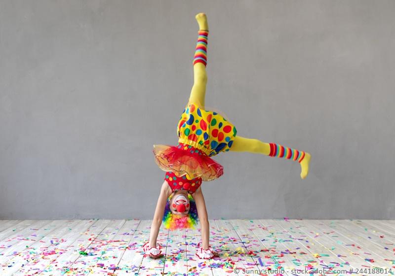 Mädchen als Clown verkleidet macht einen Radschlag