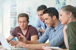 3 junge Männer sitzen gemeinsam an einem Laptop