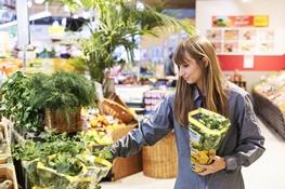 Auszubildende bei REWE sortiert Obst und Gemüse