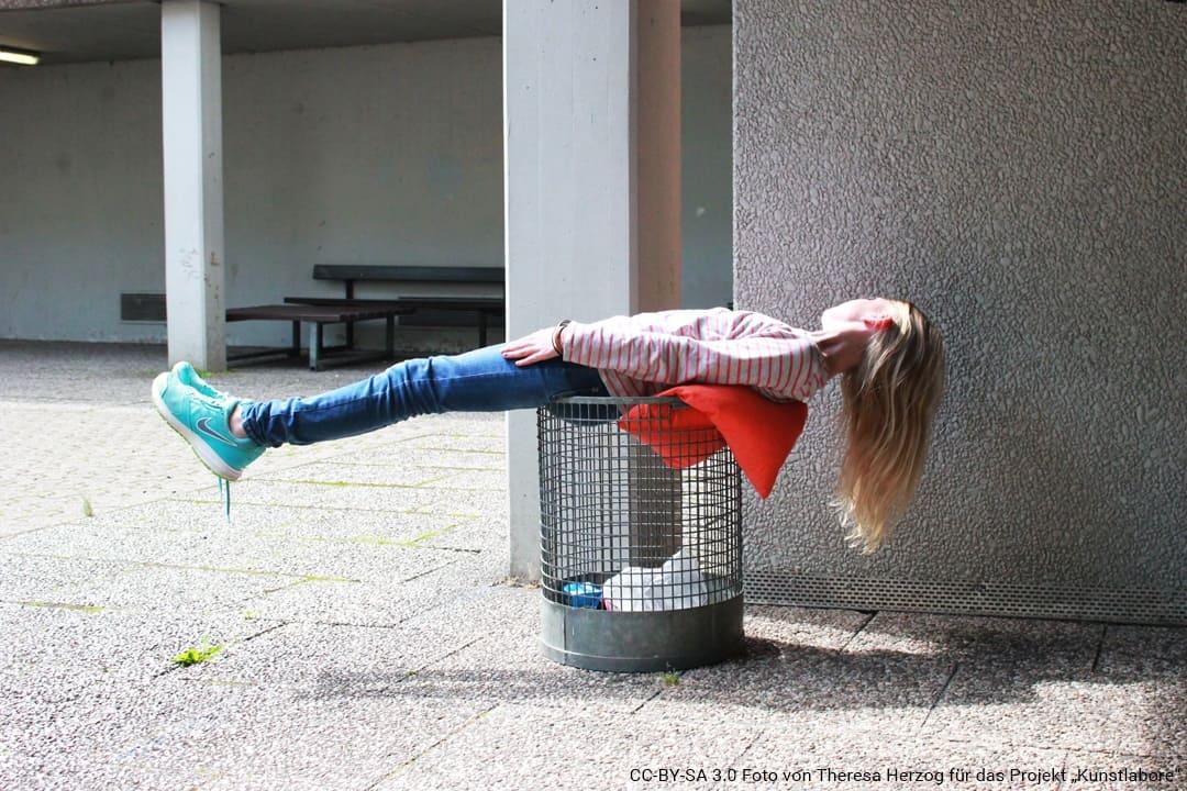 Eine Schülerin liegt quer über einem Mülleimer