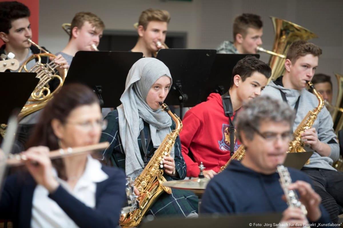 Die Bläserklasse einer Schule musiziert mit einem Orchester
