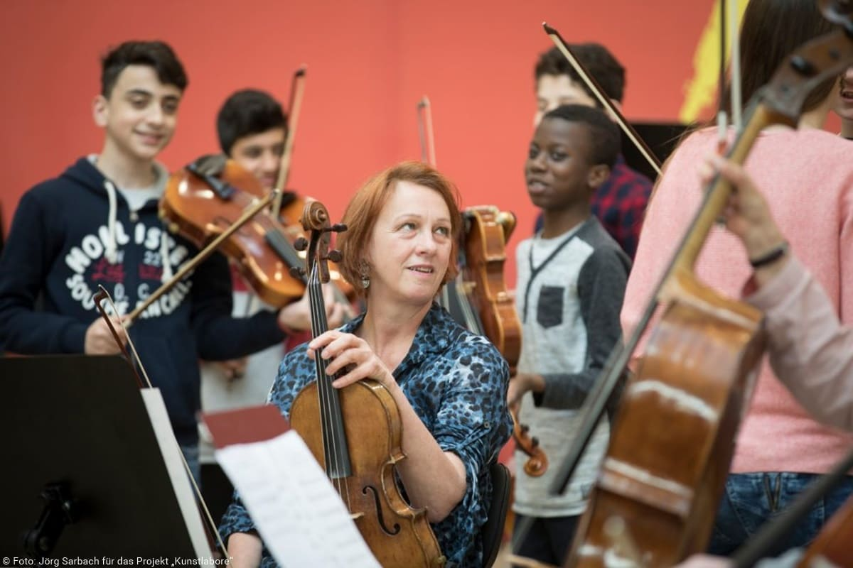 Lehrerin und Schüler mit Streichinstrumenten