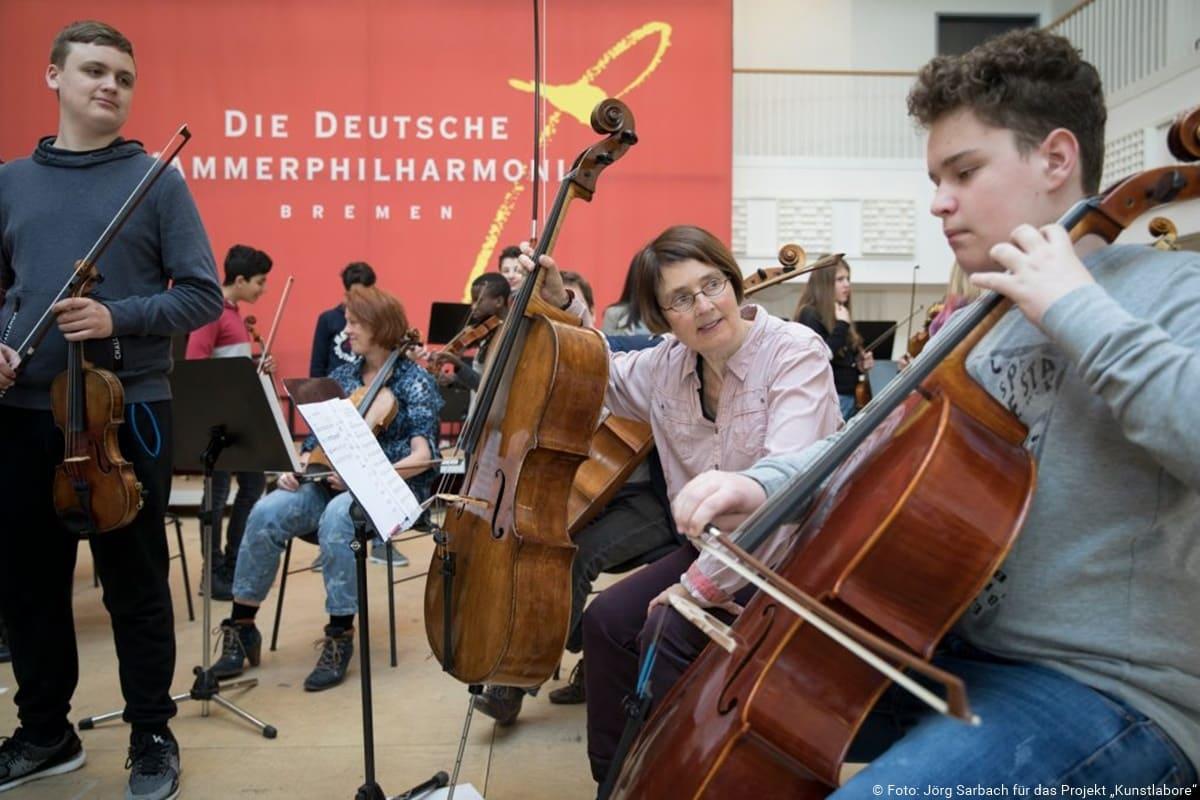 Musiker der deutschen Kammerphilharmonie musizieren mit Schülern