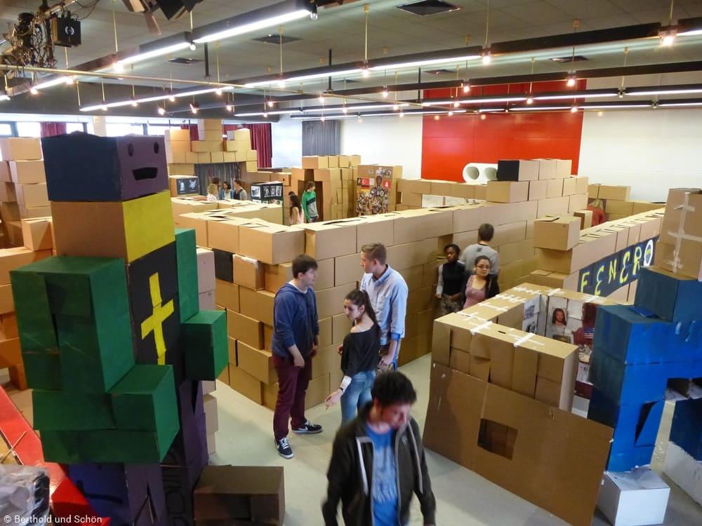 Schüler laufen durch Labyrinth von Kisten