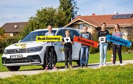 Kinder mit Schildern vor einem SUV (Reaktionsweg + Bremsweg = Anhalteweg)