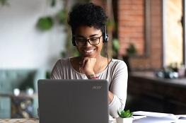 Frau sitzt mit Headset am Laptop