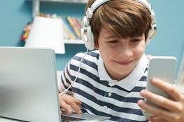 Junge mit Kopfhörer am Smartphone und Laptop