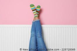 Beine mit warmen Socken an den Füßen vor der Heizung