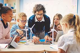 Lehrer mit Schulklasse, Windräder und Tablet