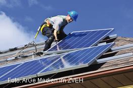 Mann installiert Photovoltaikanlage auf Dach